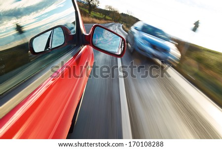 A man driving a red car towards an oncoming vehicle. - stock photo