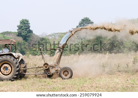 a man driving tractor mower in a field with trees in the background - stock photo
