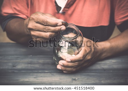 A man drops money into a glass jar for a savings