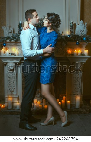 A man embraces a woman in a room near the fireplace, around burning candles. - stock photo