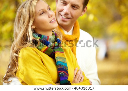 A man embracing his girlfriend against autumn background