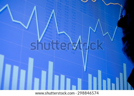 A man examining a business chart on an LCD screen. Could also be a scientific graph. - stock photo