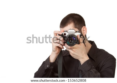 A man facing the camera holds a camera prepared to press the shutter button and take a photograph.  - stock photo