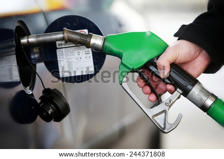 A man filling a car with petrol - stock photo