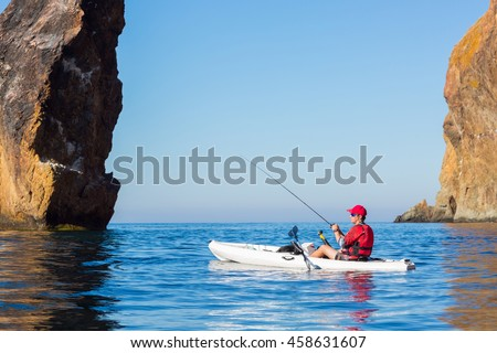 A man fishing on a kayak boat in the sea near the rocks at the shore of island mountain. Fisherman kayaking. Young fisherman kayaking.
