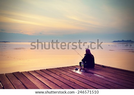 A man fishing on a lake at sunset in Vintage tone - stock photo