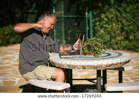 A man frustrated with his lack of wireless connection and or computer skills takes his anger out by punching his laptop to pieces - stock photo