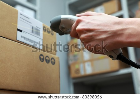 A man gets on the hip scaner in operations directed on printed barcode. Warehouse scene. Shallow DOF!