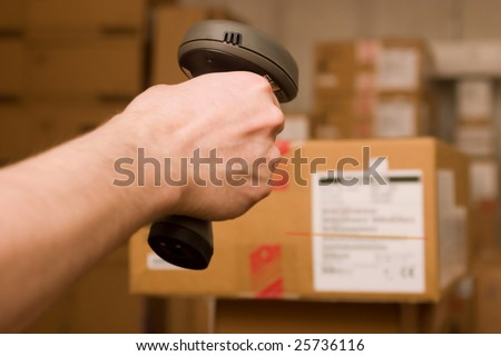 A man gets on the hip scanner in operations directed on printed barcode. Warehouse scene. - stock photo