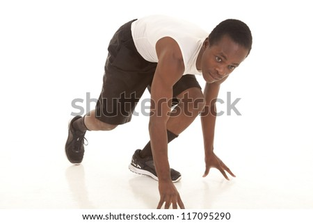 A man getting ready to run, he is down in his runners stance. - stock photo