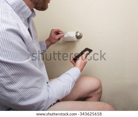 A man getting toilet paper while using his phone on the toilet - stock photo