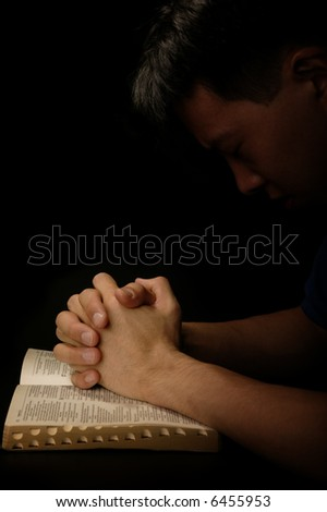 a man give thanks to god. praying with bible open - stock photo