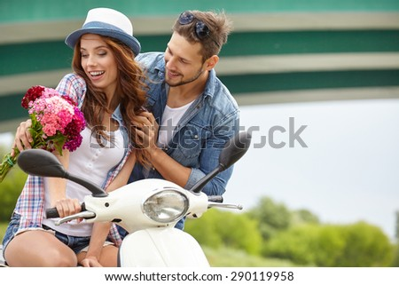 A man gives flowers beautiful woman. In the background the river and scooter - stock photo