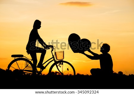 a man giving a big heart to a woman riding a bicycle silhouette - stock photo