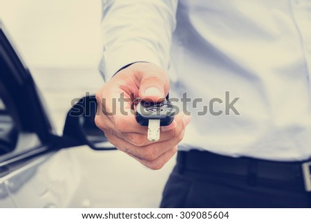 A man giving car key, vintage tone image - stock photo