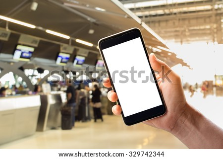 A man hand holding empty screen of smart phone and check-in counter airport terminal background. - stock photo