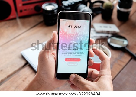A man hand holding screen Apple music app showing on iPhone 6 plus in his office. Apple Music is the new iTunes-based music streaming service that arrived on iPhone.CHIANG MAI,THAILAND - SEP 30,2015 - stock photo