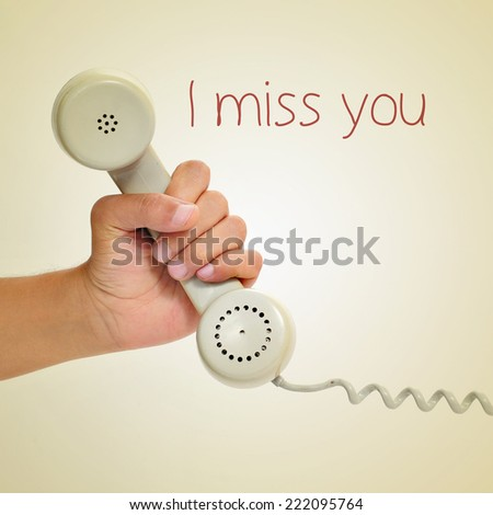 a man hand holding the handset of a telephone and the text I miss you, with a retro effect - stock photo