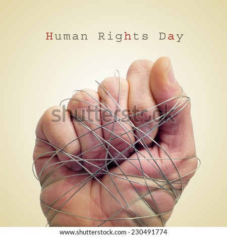 a man hand tied with wire and the text human rights day on a beige background - stock photo