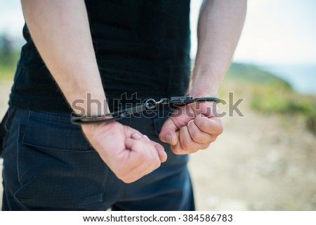 A man hands in handcuffs behind his back. Selective focus with shallow depth of field.