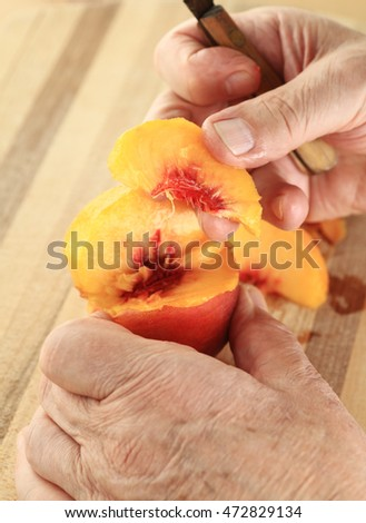 A man has cut a slice from a fresh, juicy peach.