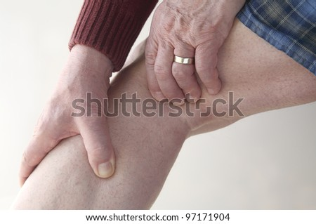 a man has soreness in the back of his knee and calf - stock photo