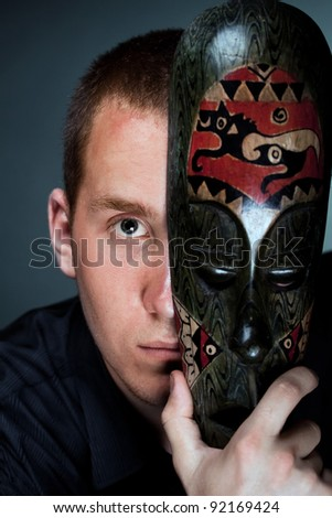 A man hiding behind a wooden antique mask (Sketch - hide suspense, mystery) on a dark background studio - stock photo