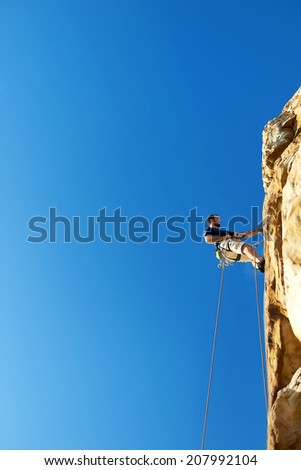 A man high up the cliff of a mountain climbing going down by rope - Rock climbing - stock photo
