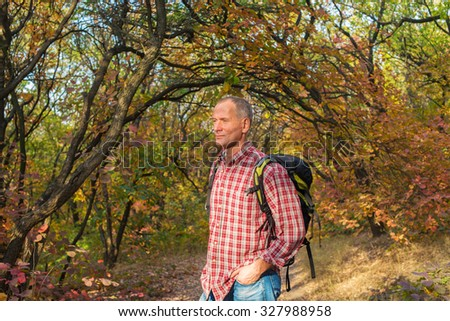 A man hiker with backpack rests in  in thought in the wonderful autumn forest. Active man is standing on the background of colorful autumn leaves. Beautiful sunny day. - stock photo