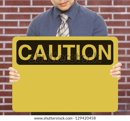 A man holding a blank caution or safety sign (with a brick wall background)