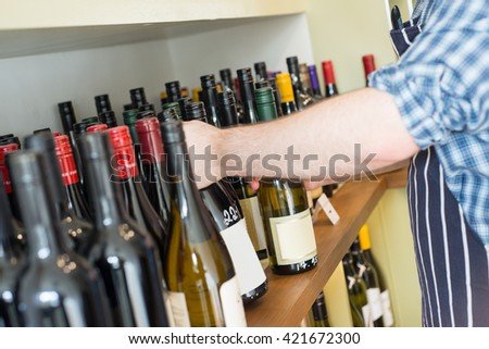 A man holding a bottle of wine from a shelf full of wine