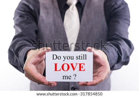 A Man holding a business card with the words, do you still love me, written on it. - stock photo