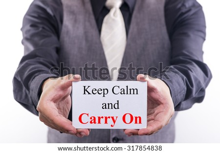 A Man holding a business card with the words, keep calm and carry on, written on it. - stock photo