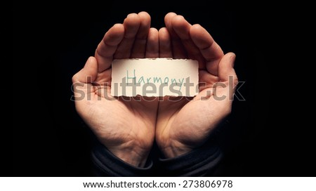 A man holding a card with a hand written message on it, Harmony. - stock photo
