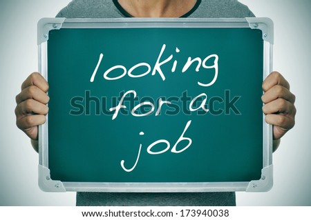 a man holding a chalkboard with the text looking for a job written on it - stock photo