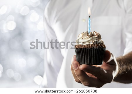 A Man holding a cupcake with a candle in a silver lights background. - stock photo