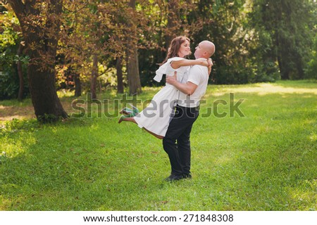 A man holding a happy girl in her arms, she was with a wedding bouquet in hand, they are happy and laughing, lifestyle-concept - stock photo