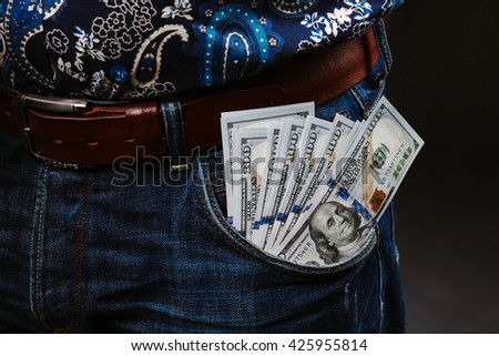 A man holding a lot of money. Banknotes of 100 dollars in different pockets, the concept of corruption. - stock photo