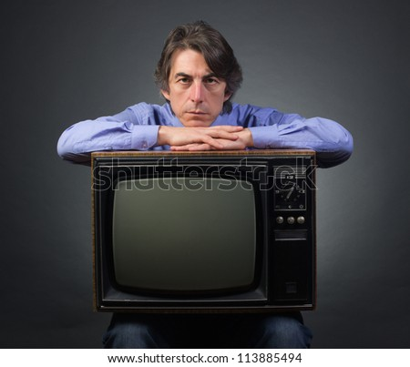 A man holding a retro television set sitting on a dark background. - stock photo