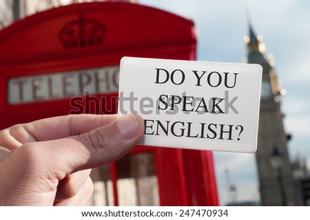 a man holding a signboard with the text do you speak english? with a red telephone booth and the Big Ben in the background, in London, UK - stock photo