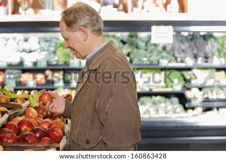 A man holding an apple in shop