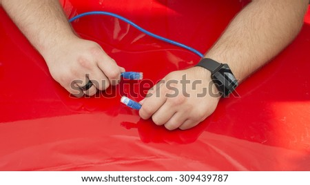 A man holding an Ethernet cable.