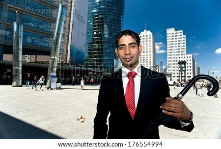 A man holding an umbrella while standing in front of skyscrapers.