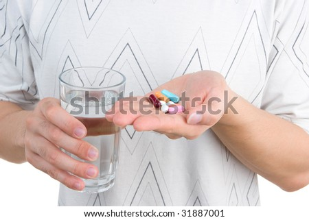 A man holding his medicine on his palm, while the other hand holding a glass of water.