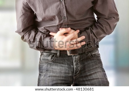 A man holding his stomach because he has diarrhea