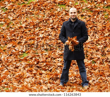 A man holding leaves at the park
