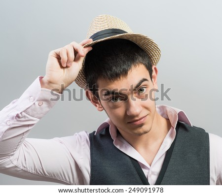 a man holding on to his western hat in his duster without a shirt. - stock photo
