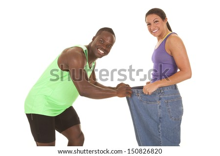 A man holding on to the front of a woman's pants with a smile on their faces, because she lost weight. - stock photo