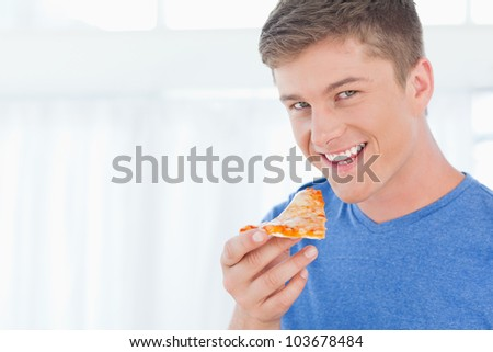 A man holding some pizza as he looks at the camera and smiles - stock photo