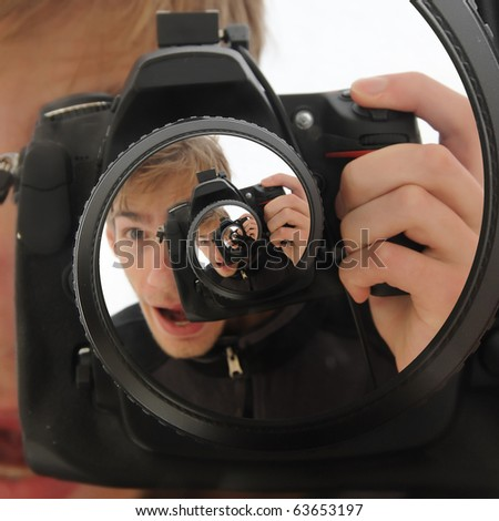 A man holding up a DSLR camera taking a never ending picture. The name for this effect is called the droste effect. - stock photo